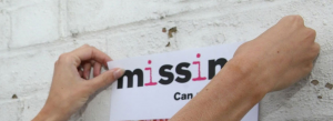 Close-up of hands putting up a Missing People poster